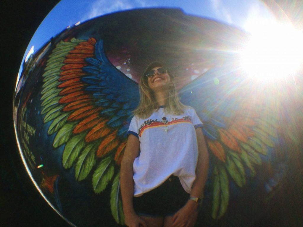 Paula Falcão, do time Aproveite, posa em frente à grafite com asas