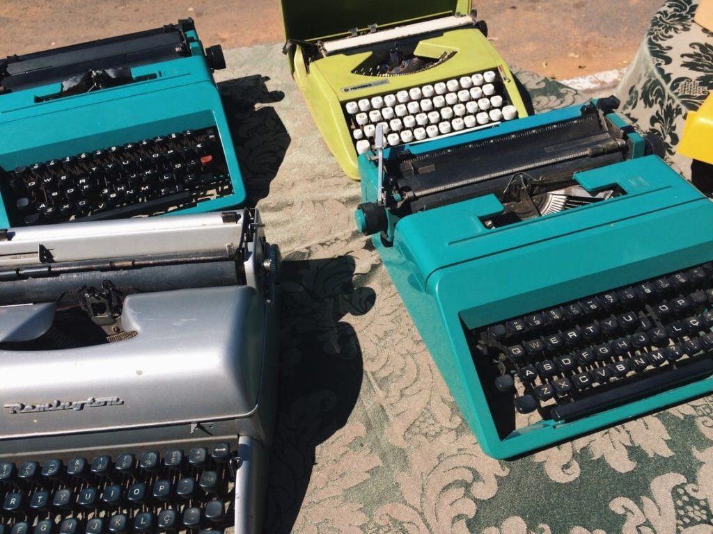 Máquinas de escrever expostas em mesas postas na calçada durante a feira mensal promovida pelo Brechó Goiano