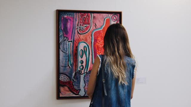 Paula Falcão observa obra no Museu de Arte de Goiânia